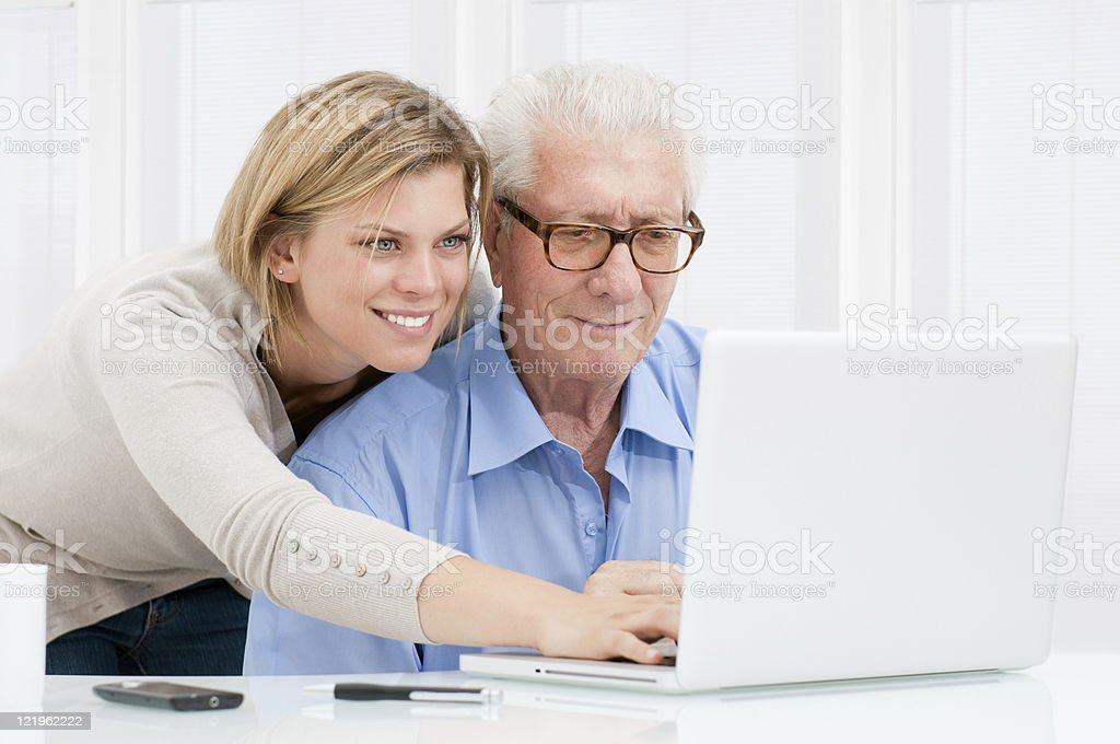 Young woman helping older man on laptop stock photo