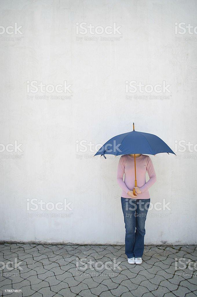 Young woman hidden under umbrella royalty-free stock photo