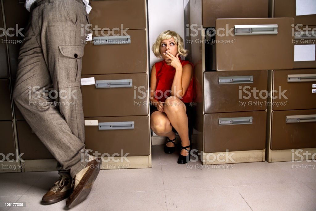 Young Woman Hiding and Smoking Between Filing Cabinets royalty-free stock photo
