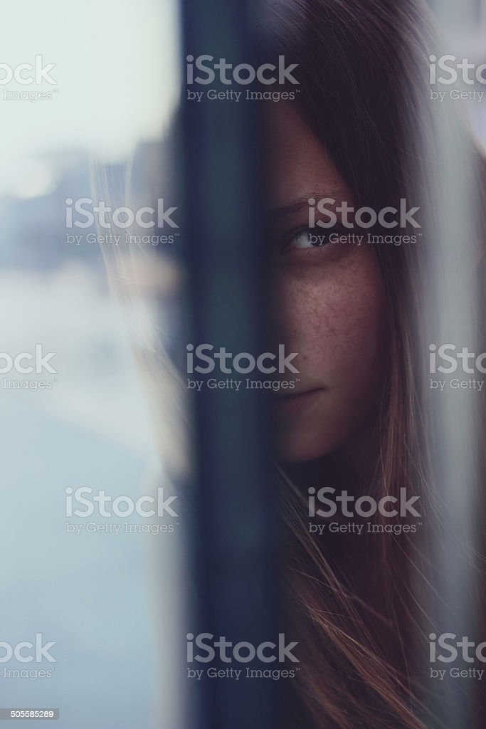 Young woman hiding behind the glass stock photo