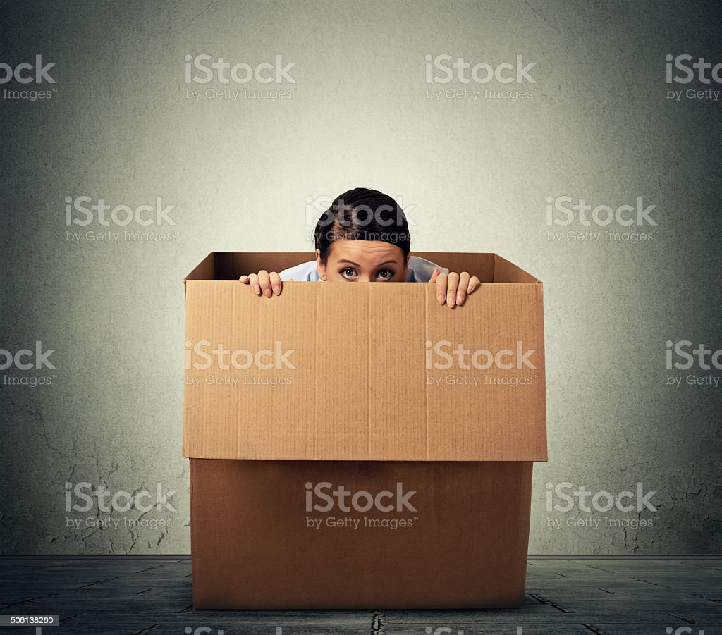 Young woman hiding in a carton box stock photo