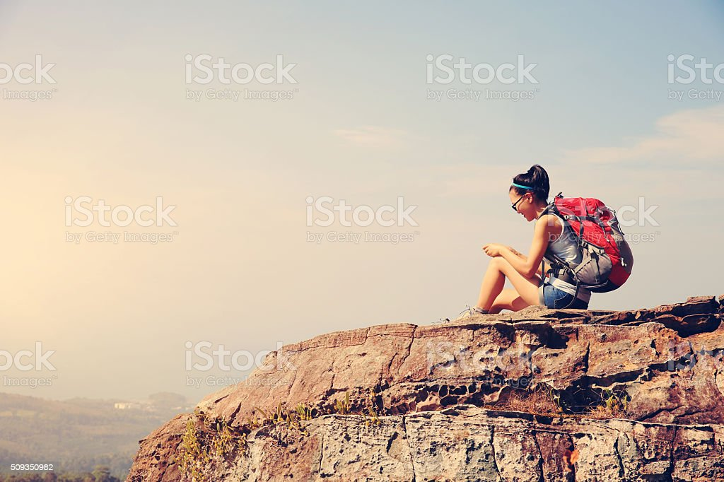 young woman hike use smart phone at mountain peak stock photo