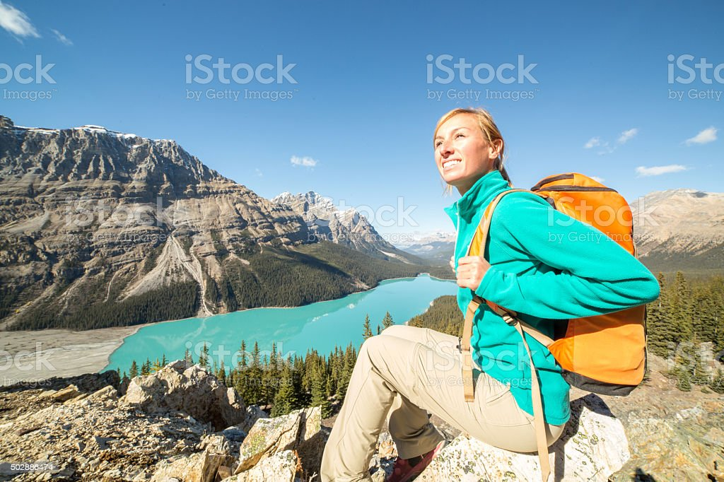 Young woman hiker at mountain top looking at view. stock photo