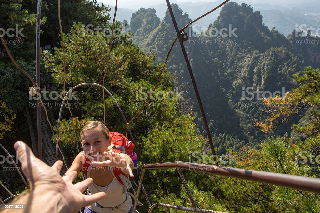 Young woman hiker climbing to the top, helping hand stock photo