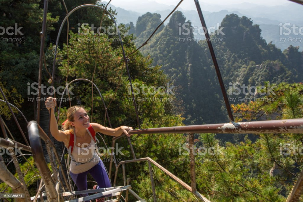 Young woman hiker climbing to the top stock photo