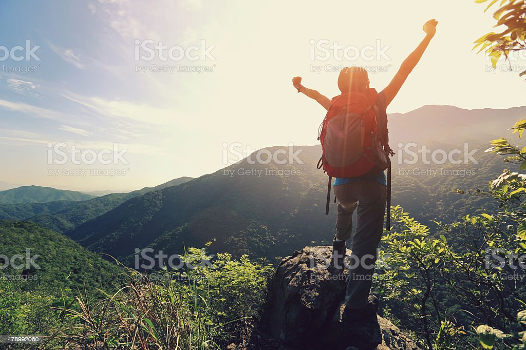 young woman hiker open arms moutain peak stock photo
