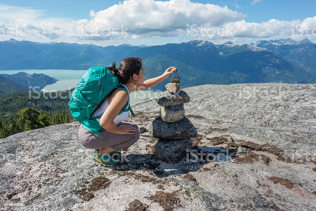 Young Woman Hiker Placing Rock on Cairn on Mountain Summit stock photo