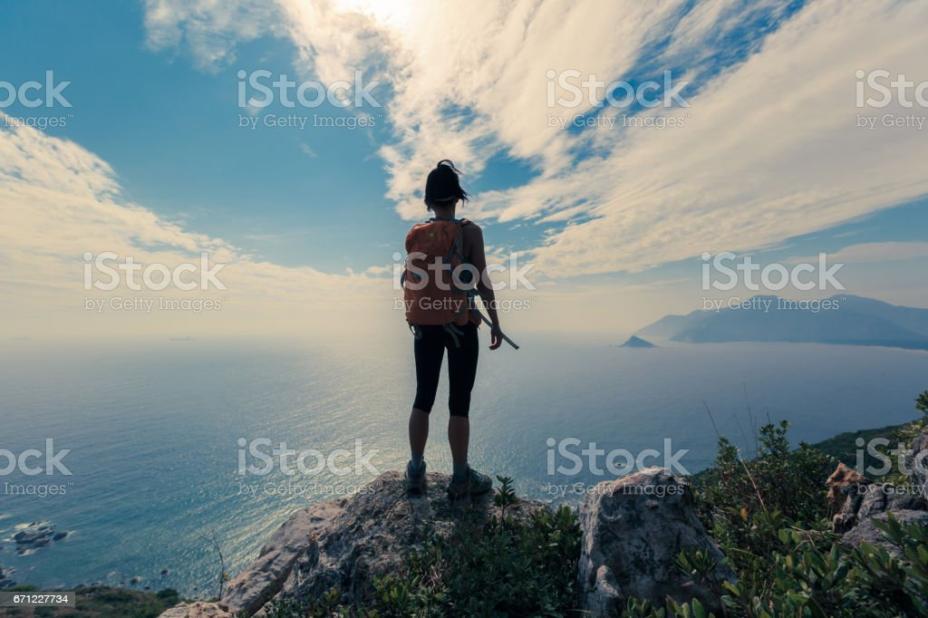 young woman hiker standing on mountain peak stock photo