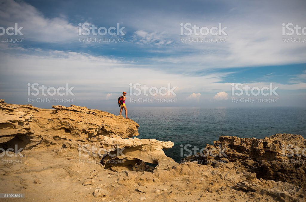 Young woman hiker standing on top of the rocks stock photo