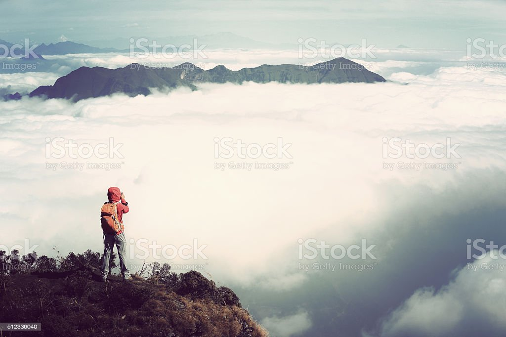 young woman hiker taking photo on beautiful mountain peak stock photo