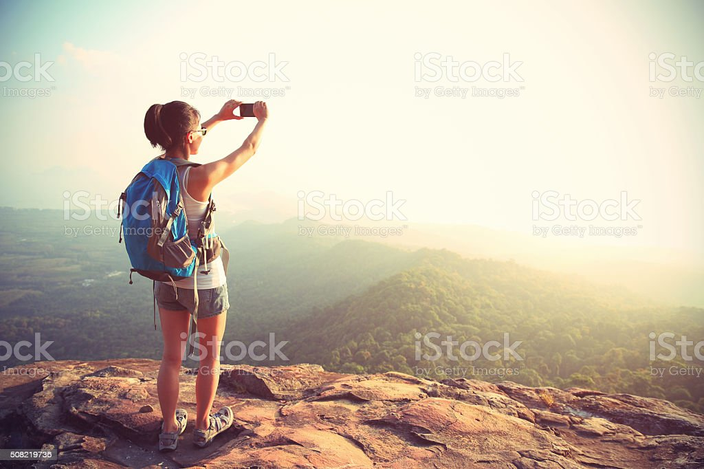 young woman hiker taking photo with smart phone stock photo