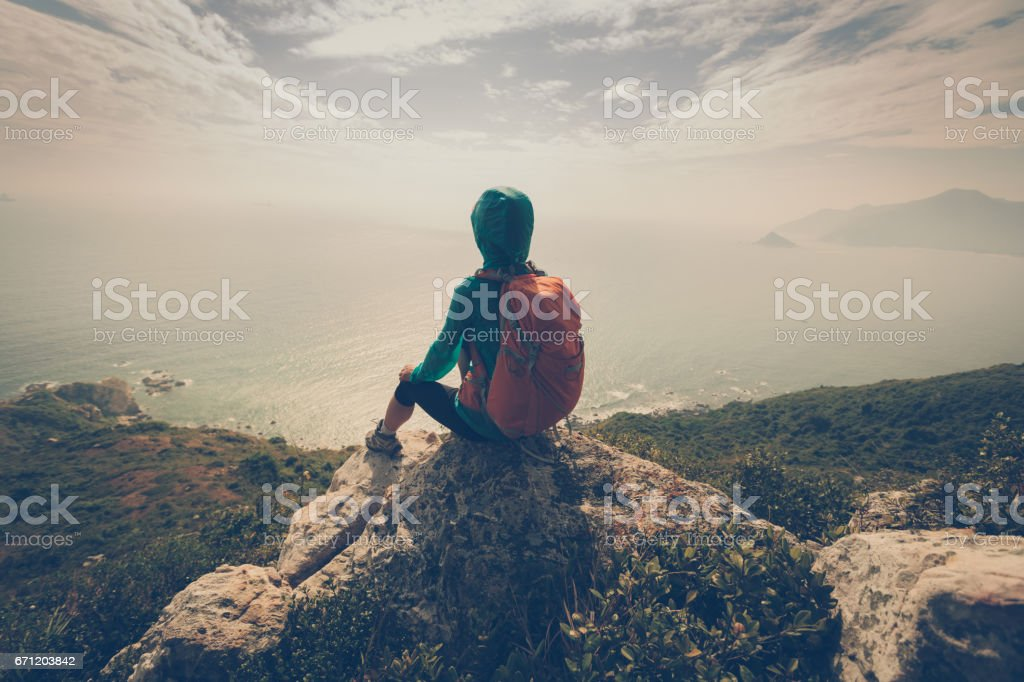 young woman hiker thinking on mountain peak stock photo