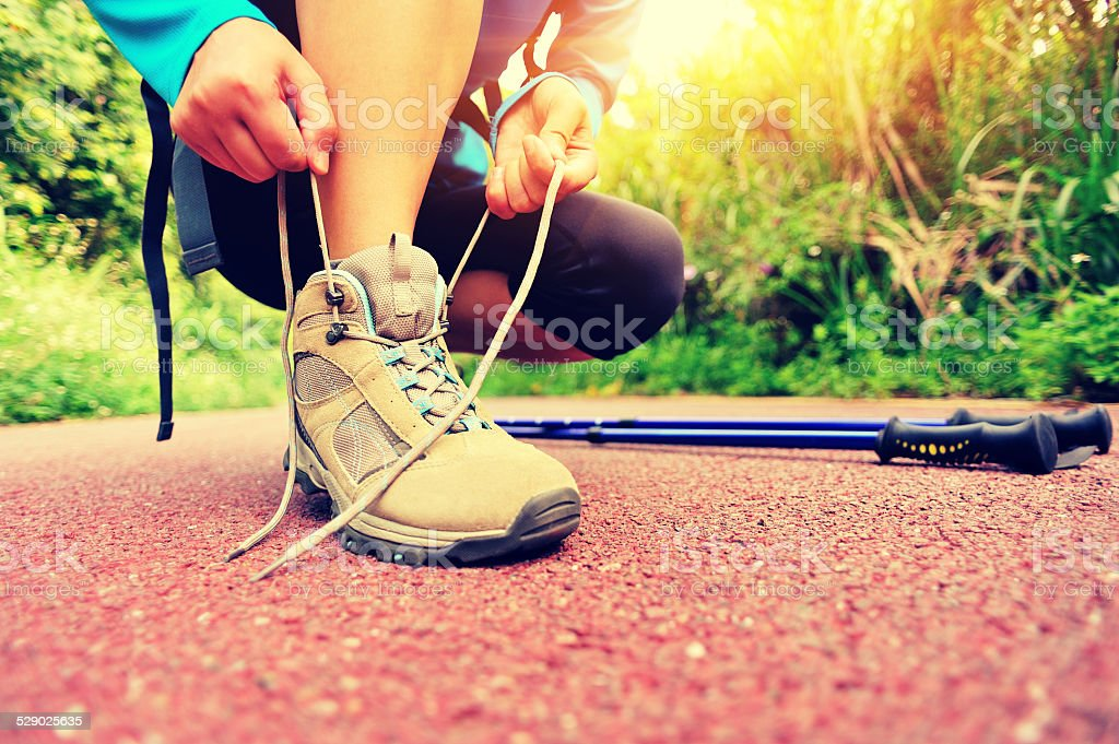 young woman hiker tying shoelace outdoor stock photo