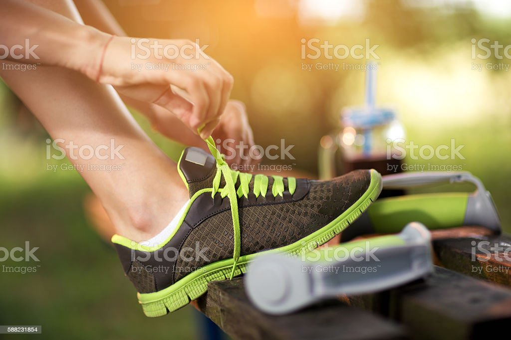 Young woman hiker tying shoelaces in the nature stock photo