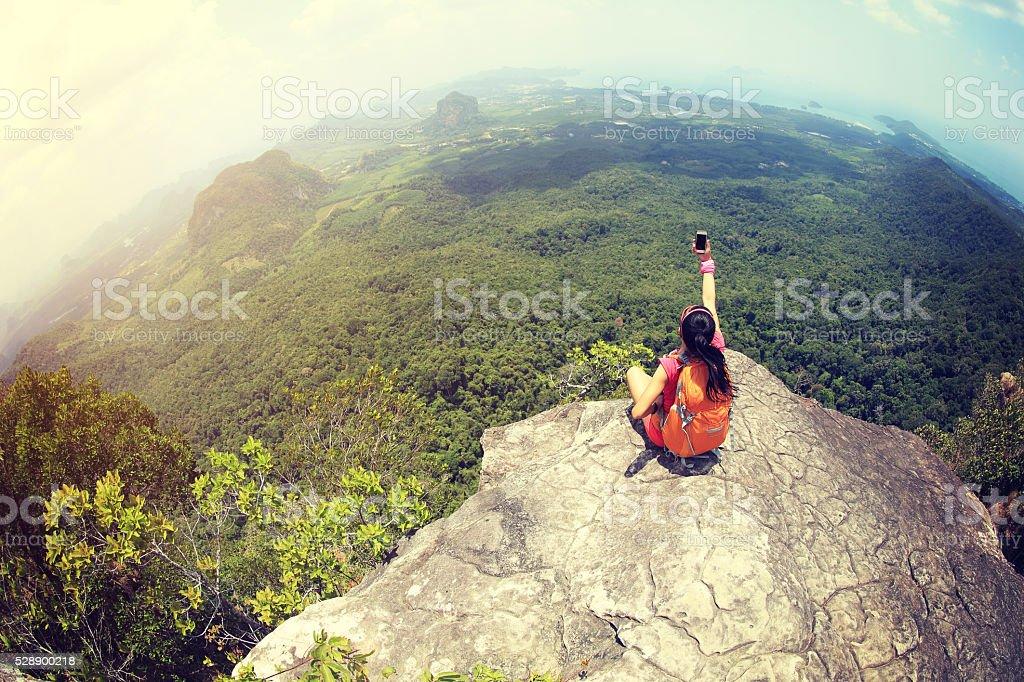 young woman hiker use smartphone taking photo on seaside mountain stock photo