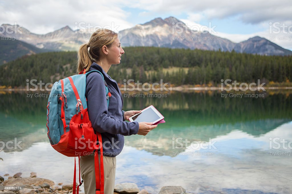 Young woman hiking by the lake using digital map stock photo