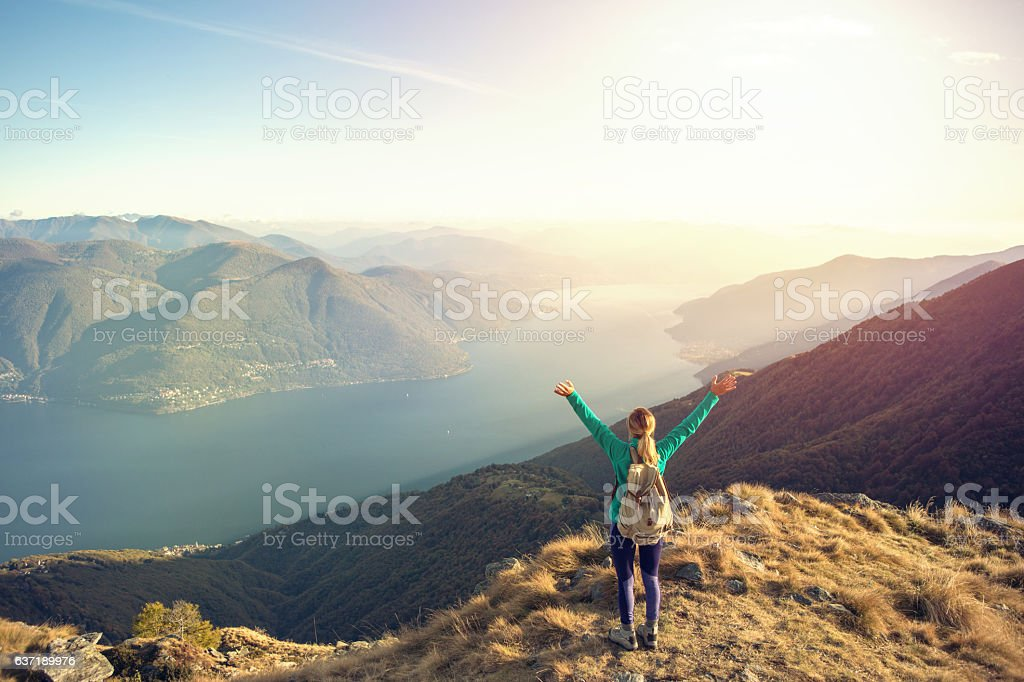 Young woman hiking celebrates at mountain top stock photo