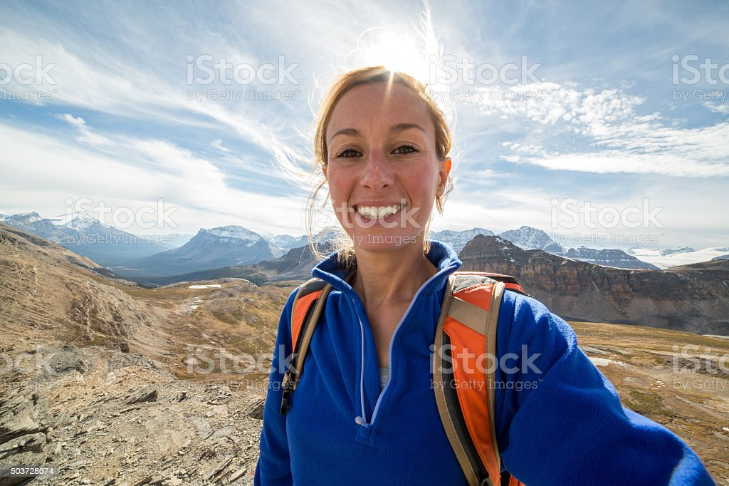 Young woman hiking in Autumn takes a selfie portrait stock photo