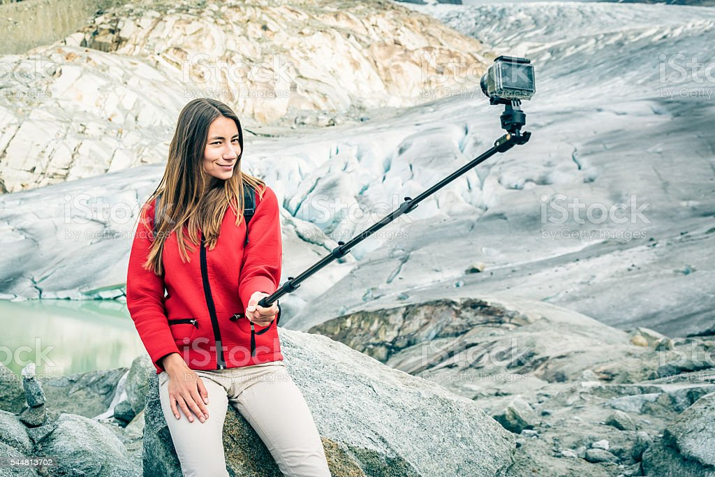 Young Woman Hiking in the Swiss Alps, Taking a Selfie stock photo