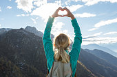 Young woman hiking makes heart shape finger frame