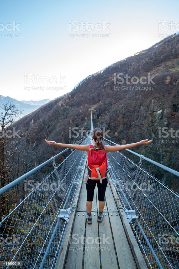 Young woman hiking on a suspension bridge arms outstretched stock photo