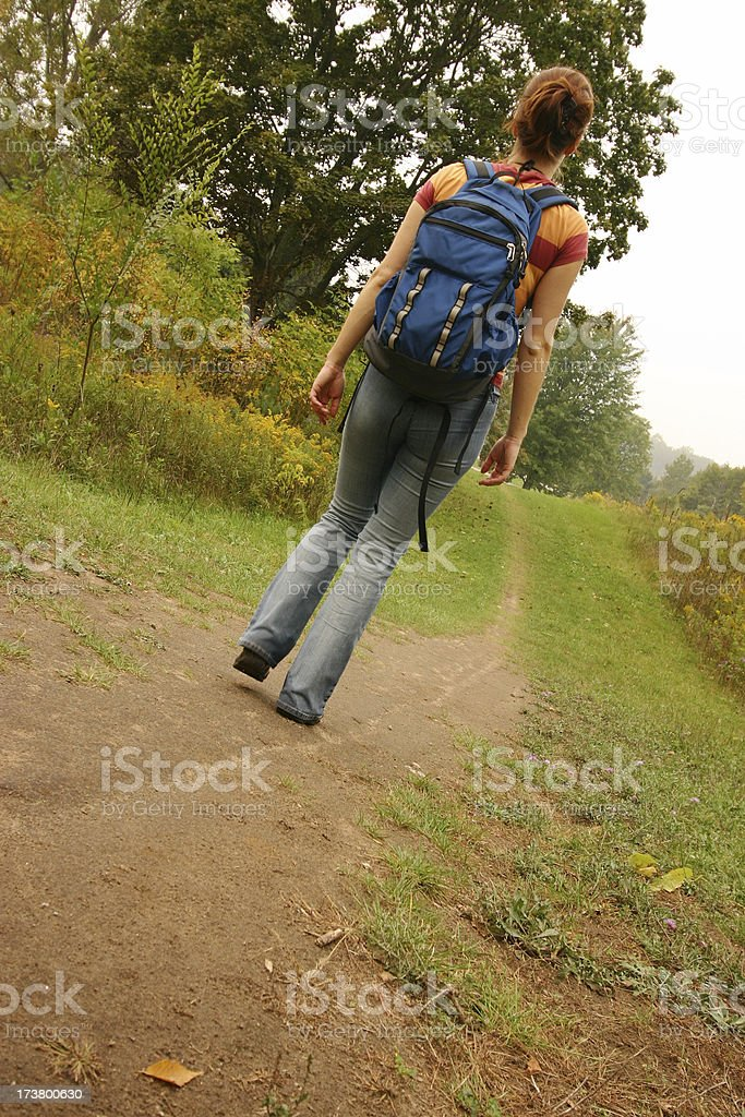 Young woman hiking on trail with backpack royalty-free stock photo