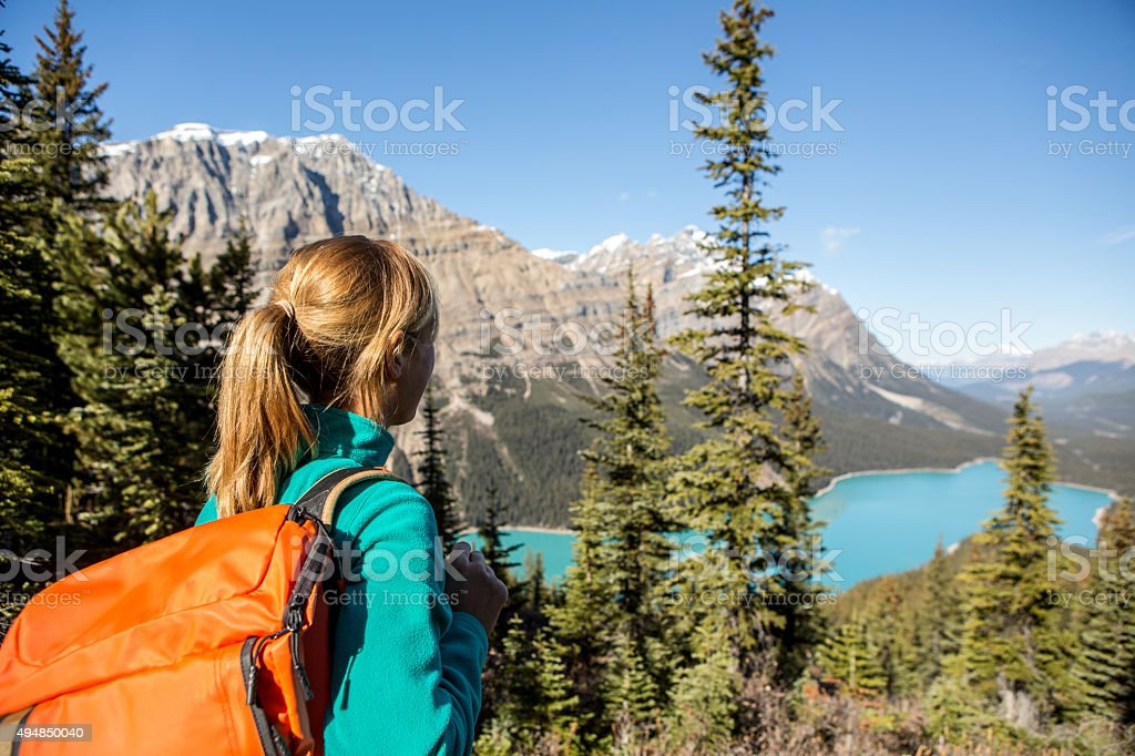 Young woman hiking overlooks the lake stock photo