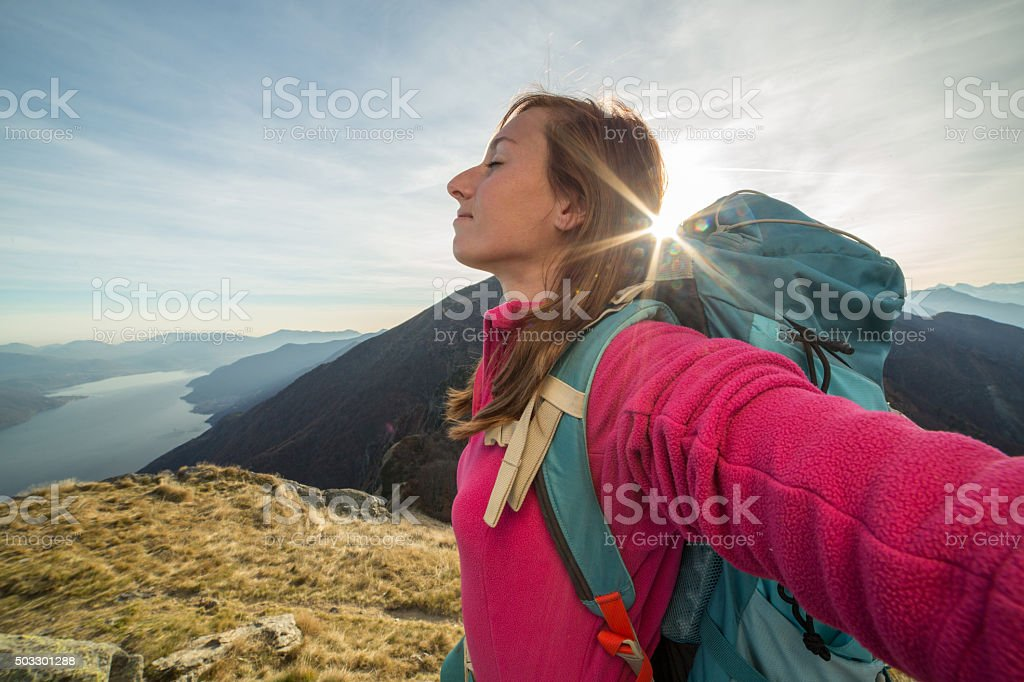 Young woman hiking reaches mountain top, outstretches arms stock photo