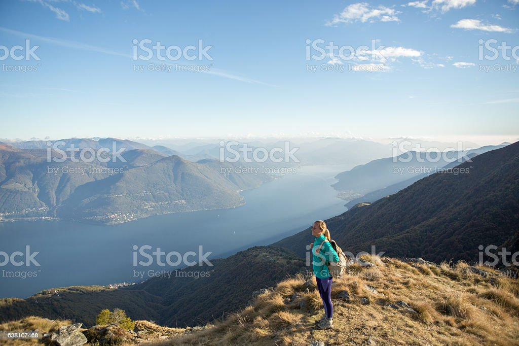Young woman hiking reaches the mountain top, contemplates view stock photo