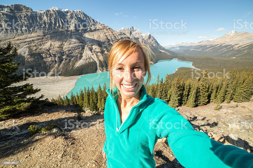 Young woman hiking reaches view point and takes selfie portrait stock photo
