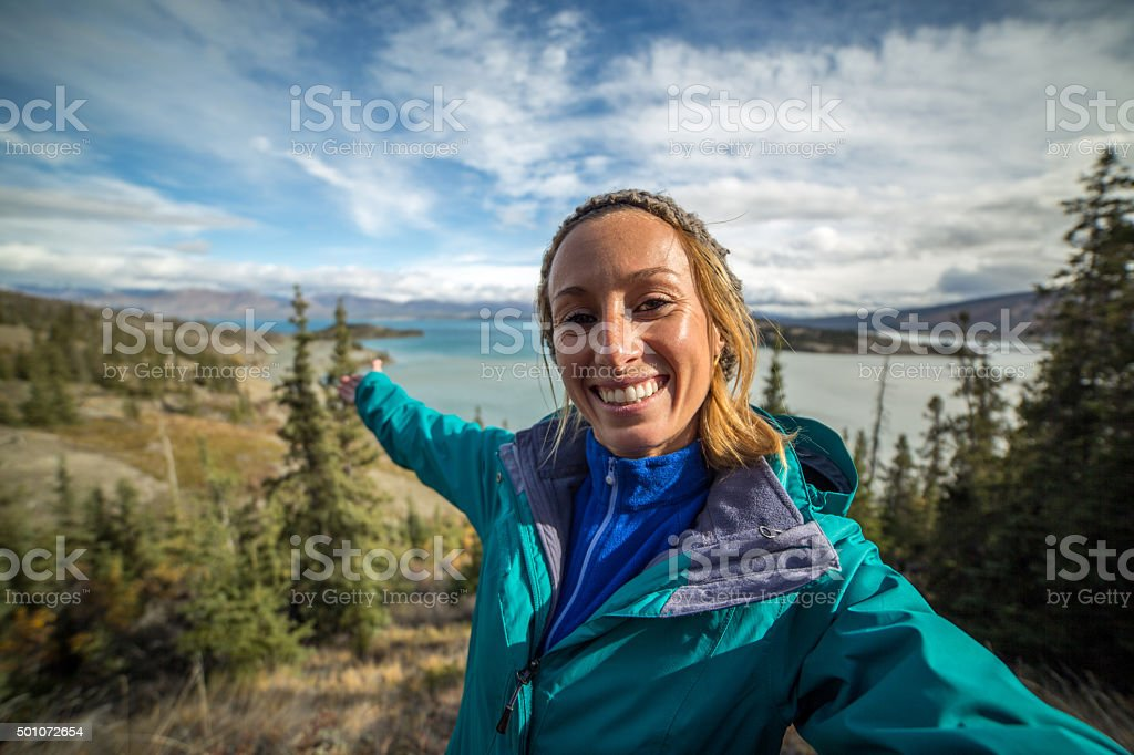 Young woman hiking reaches view point and takes selfie portrait. stock photo