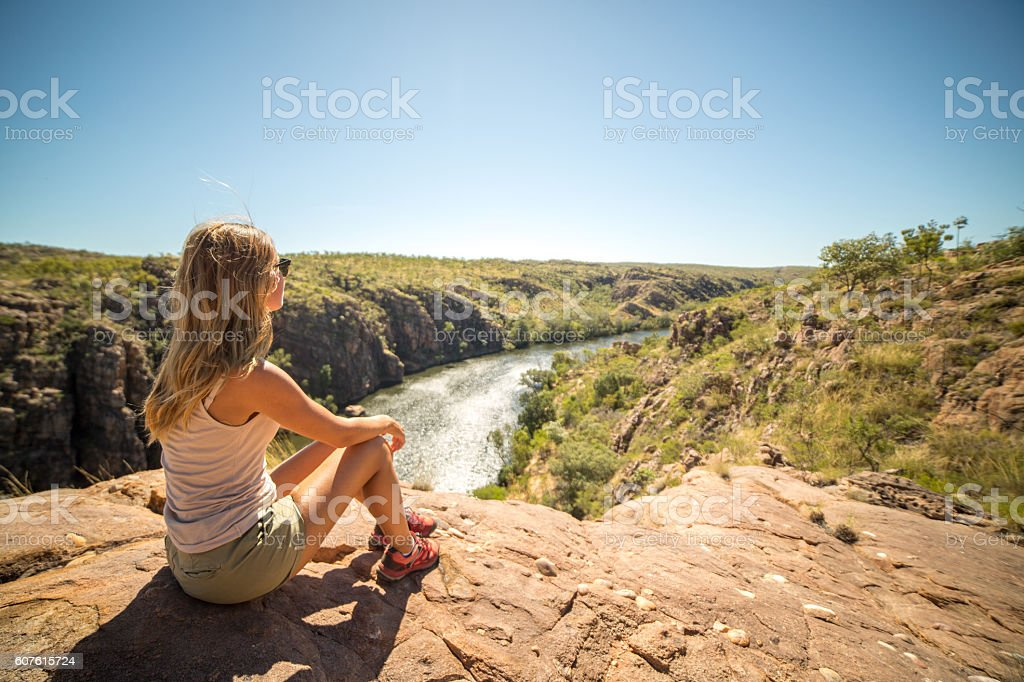 Young woman hiking sits on cliff and looks at view stock photo