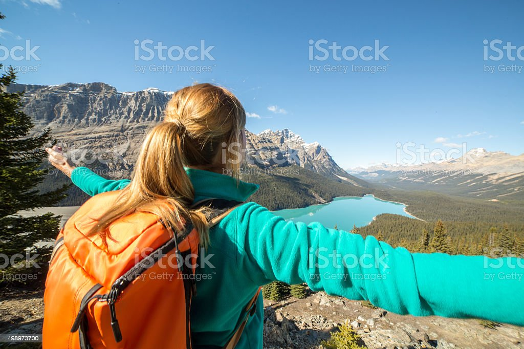 Young woman hiking stands on a mountain top arms outstretched stock photo