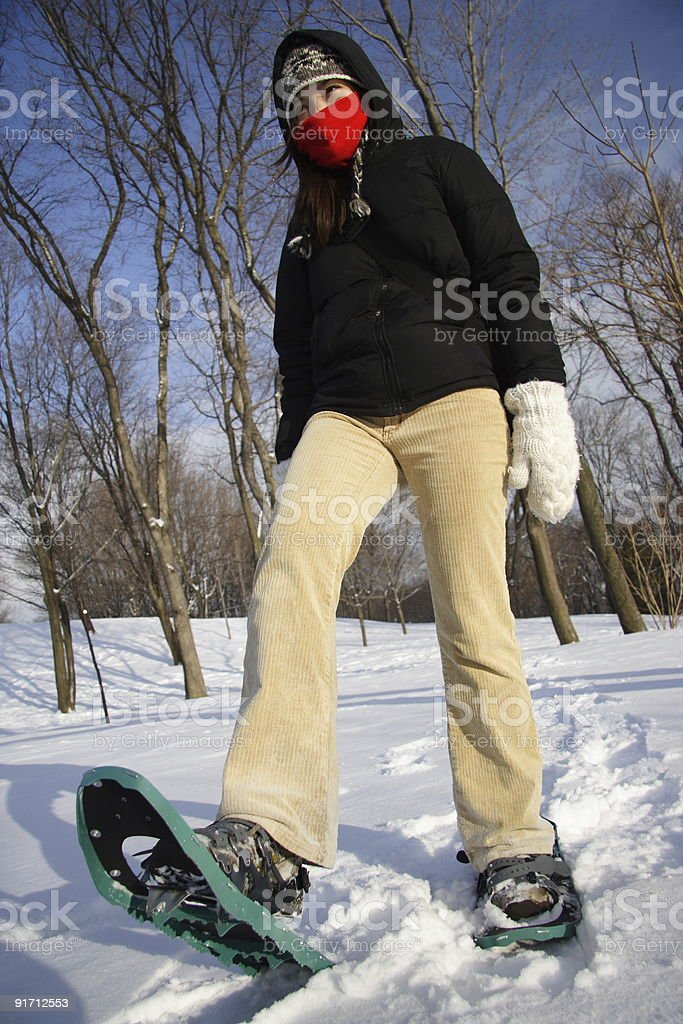 Young woman hiking with snowshoes / rackets royalty-free stock photo