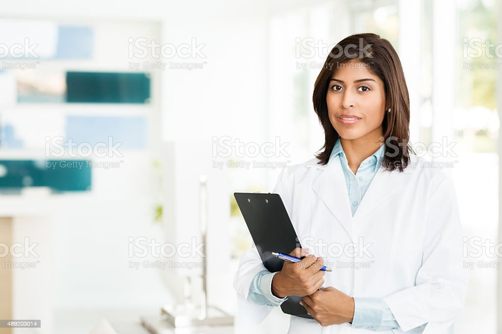 Young Woman Hispanic Doctor Nurse in Office stock photo