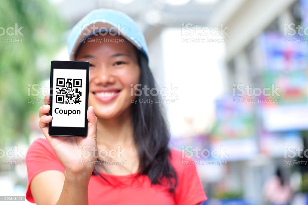 young  woman hold smart phone on shopping street stock photo