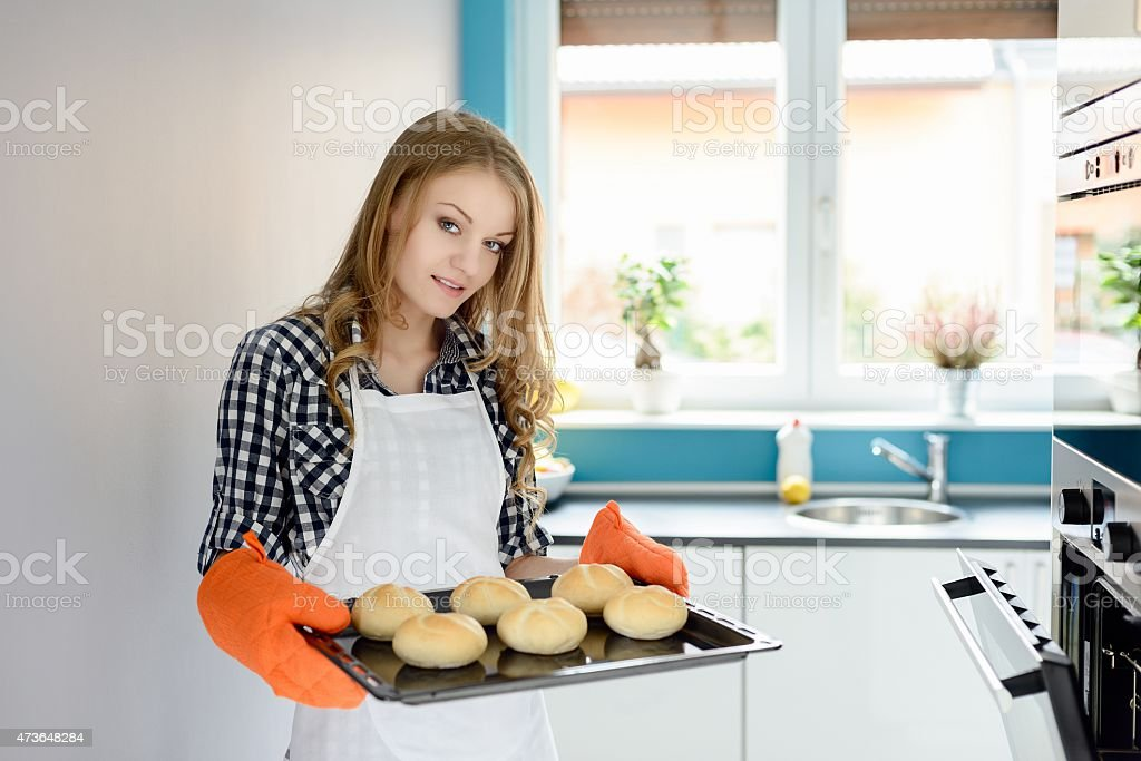 Young woman holding a baking tray with bread rolls stock photo