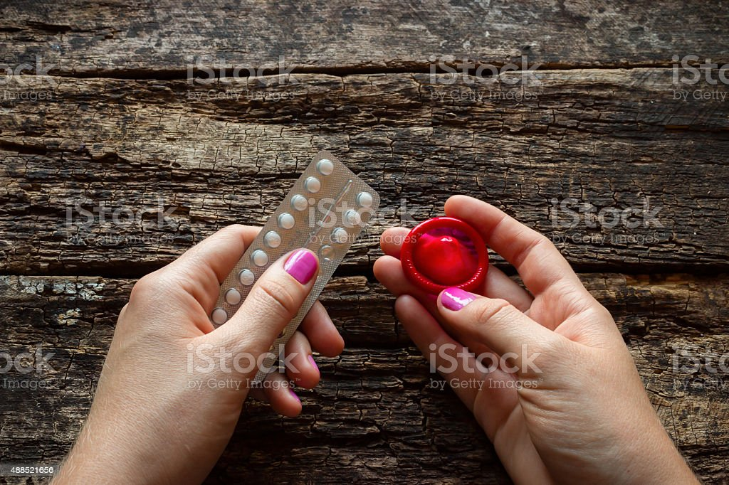 young woman holding a birth control pills and a condom stock photo