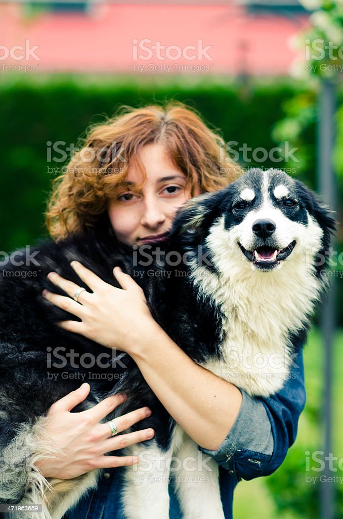 young woman holding a border collie dog in her arms stock photo