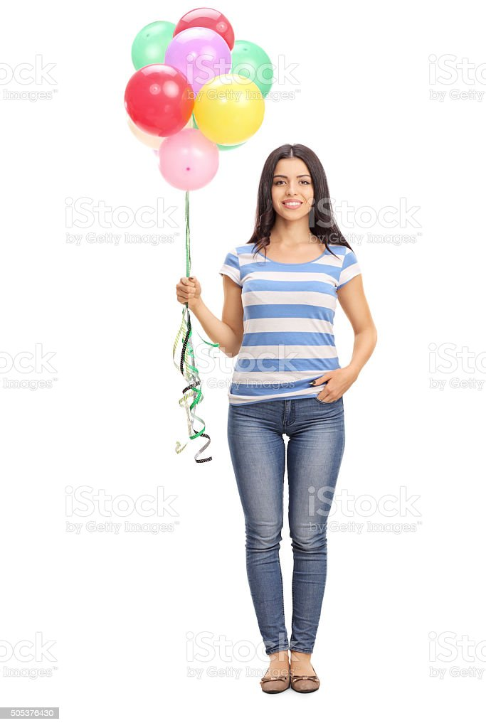 Young woman holding a bunch of balloons stock photo