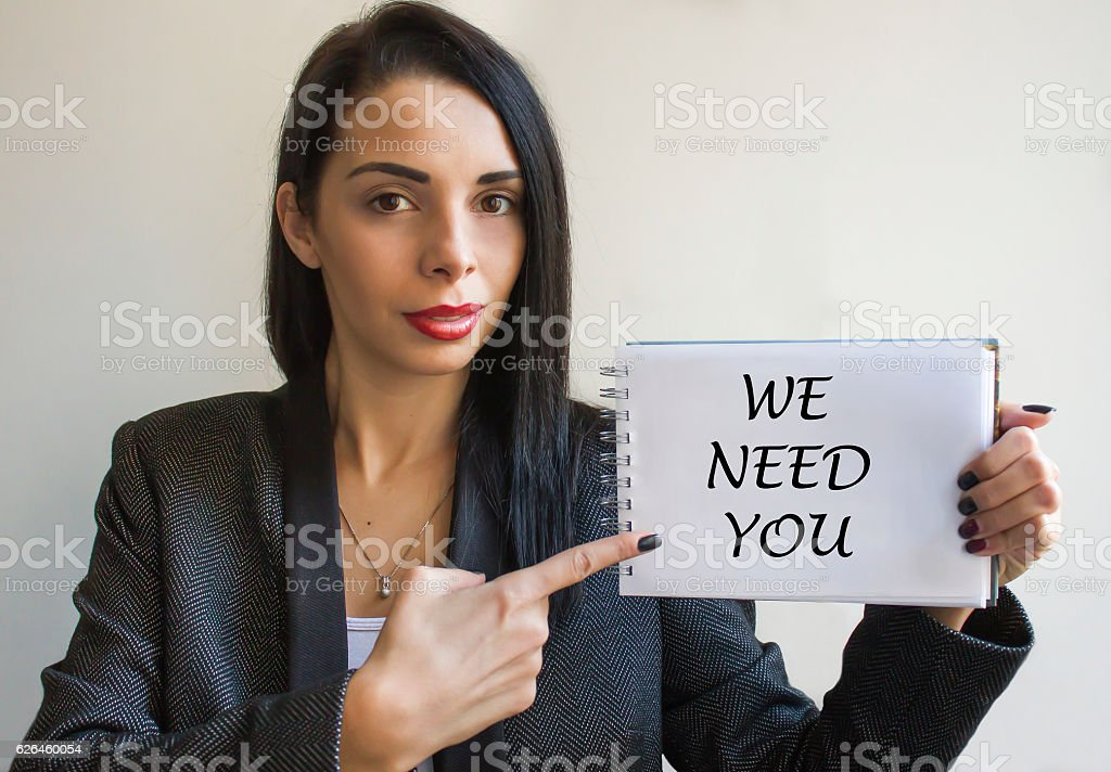 Young woman holding a cardboard sign, we need you stock photo