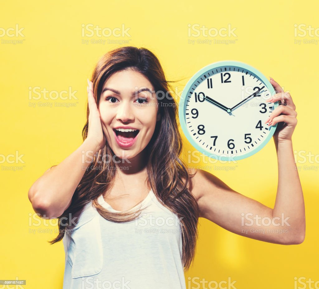 Young woman holding a clock stock photo
