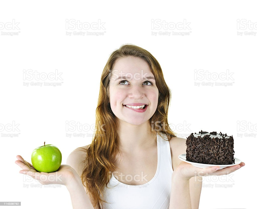 A young woman holding a green apple and chocolate cake royalty-free stock photo