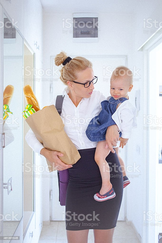 Young woman holding a grocery bag and her baby girl stock photo