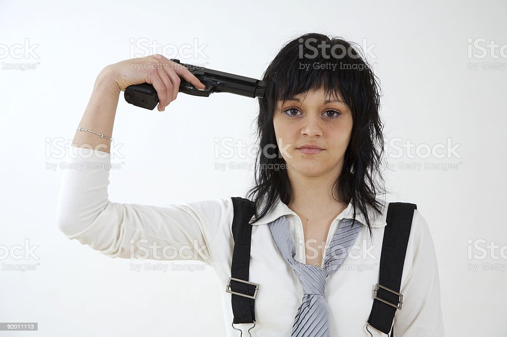 Young woman holding a gun to her own head. stock photo