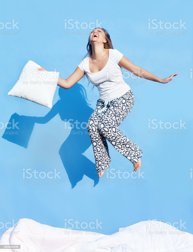 Young woman holding a pillow jumping up on bed stock photo