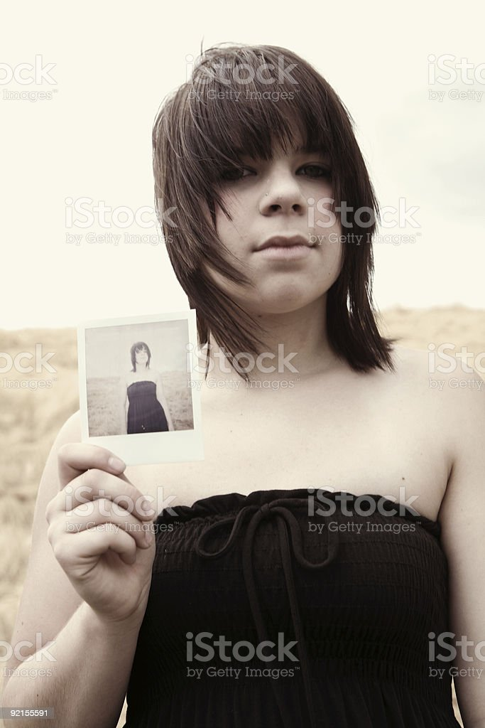 Young Woman Holding a Polaroid of Herself royalty-free stock photo
