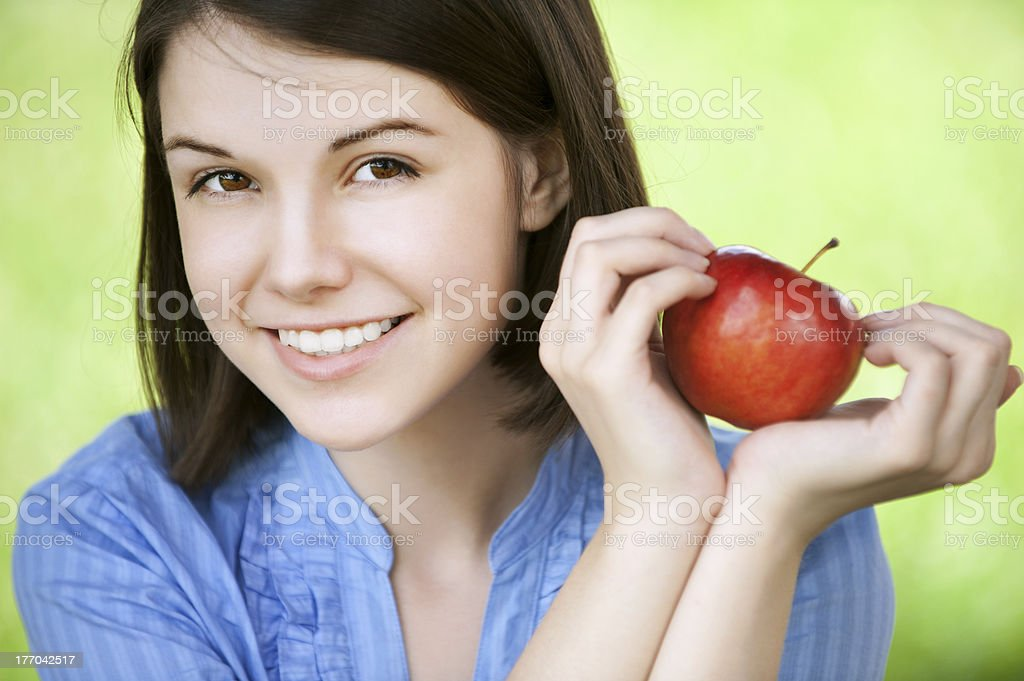 A young woman holding a red apple on a green background royalty-free stock photo