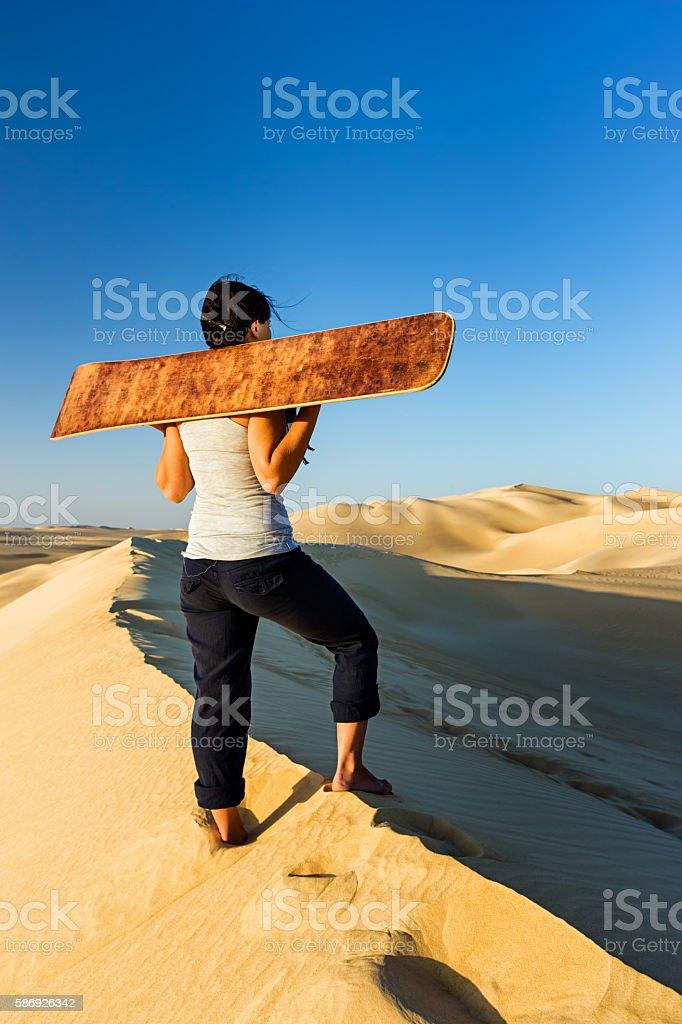 Young woman holding a sandboard, Sahara Desert, Africa stock photo