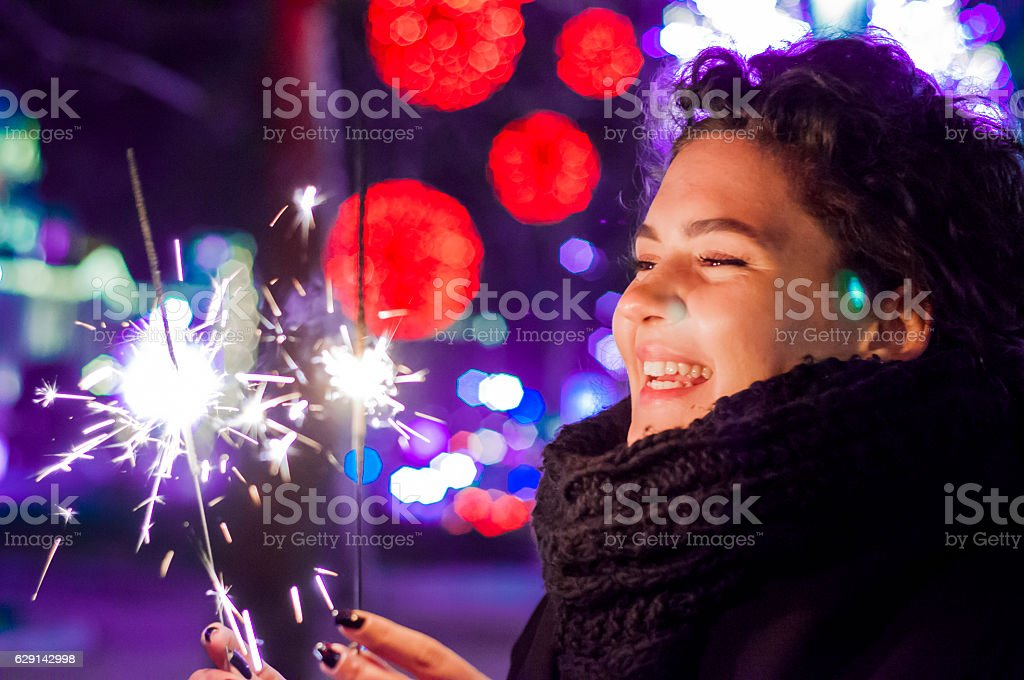 Young woman holding a sparkler lit to celebrate new year. stock photo